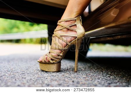 Womans Legs In High Heels. Luxury Urban Background. The Woman Is Wearing Shoes On High Heels. Close
