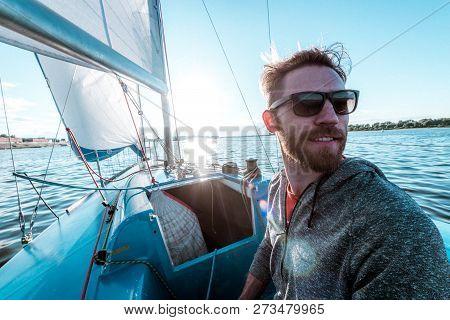 Man Controls Boat Using Tiller At Stern During Sailing On River At Summer Day
