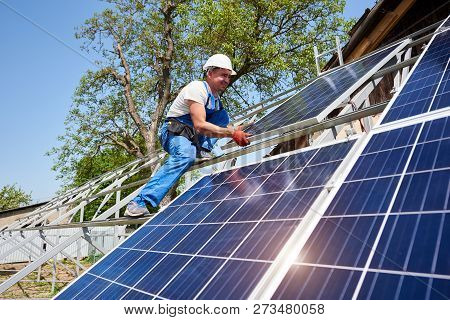 Young technician in protective helmet on tall metal platform installing heavy solar photo voltaic panel on green tree background. Stand-alone solar panel system installation, dangerous job concept. poster