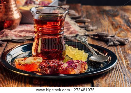 Tea in armudu glass with oriental delight rahat lokum on metal tray over wooden surface and tablecloth poster