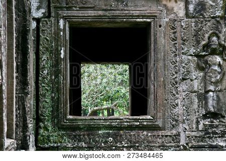Looking Through Ancient Buddhist Ruins In The Jungles Of Cambodia