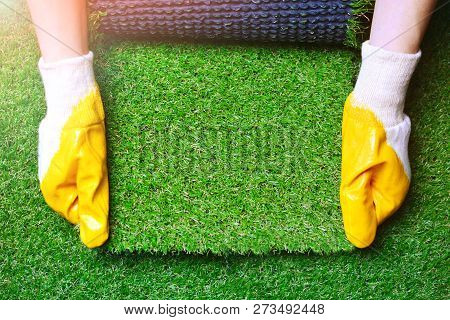 Greenering With An Artificial Grass Background. Landscape Designer Holds A Roll Of An Artificial Tur