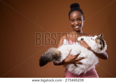 Young beautiful African Zulu woman holding cat while smiling poster