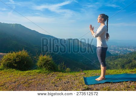 Woman doing Ashtanga Vinyasa Yoga asana Tadasana Samasthiti yoga posture in mountains in the morning