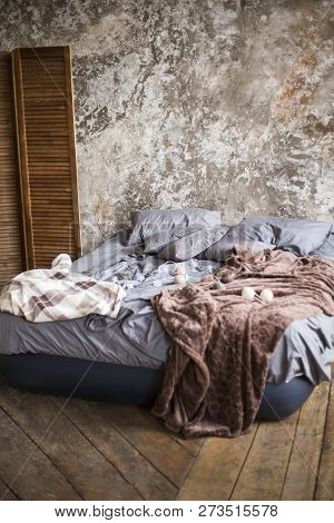 The Air Bed With Gray Bed Linen And A Brown Cover On A Wooden Floor Costs Against The Background Of