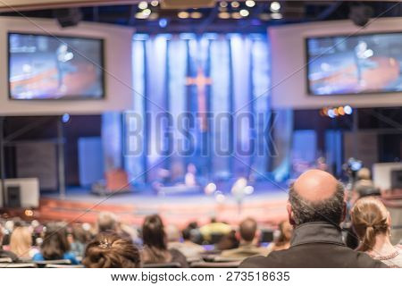 Blurry Background Rear View Audience At Bible Church With Preacher On Stage