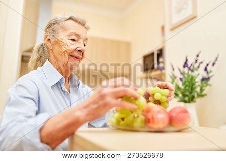 Senior woman prepares fruit for breakfast in the supervised senior citizen apartment