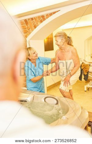 Caregiver helps senior woman while bathing in the hot tub of the senior residence