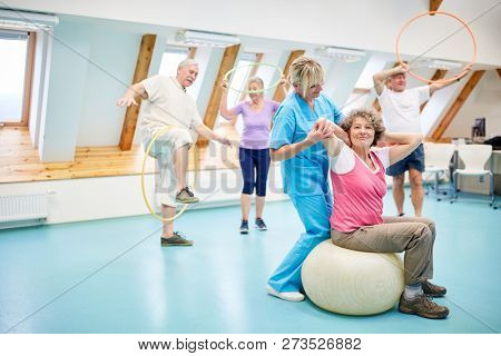 Therapist in rehabilitation course doing back exercises with senior woman in fitness center