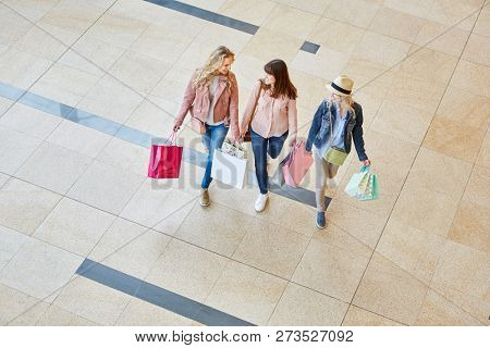 Group of young women as friends with shopping bags in shopping mall