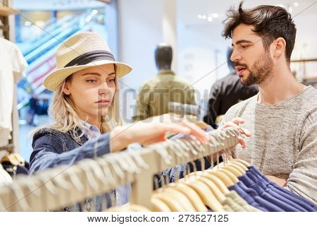 Young couple while shopping for clothes in fashion shop retail