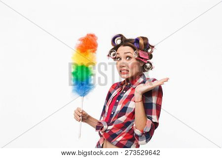 Busy housewife with curlers in hair standing isolated over white background, holding duster poster