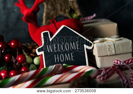 closeup of some gifts, some candy canes and some different cozy christmas ornaments, and a house-shaped black signboard with the text welcome home written in it, on a rustic wooden surface poster
