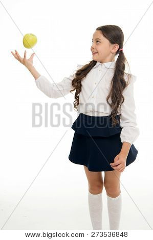Child Schoolgirl Wear Formal Uniform Hold Apple. Girl Cute Pupil Hold Apple Fruit Stand On White Bac