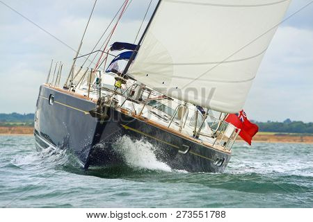 Close up of blue sailing boat, sail boat or yacht at sea with white sails