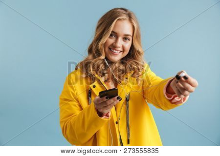 Image of pleased woman 20s wearing yellow raincoat holding mobile phone and listening to music via earphones isolated over blue background poster