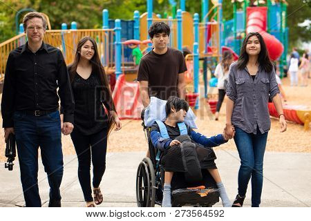 Caucasian Father And Four Biracial Teen Children Walking Past Playground With Disabled Boy In Wheelc