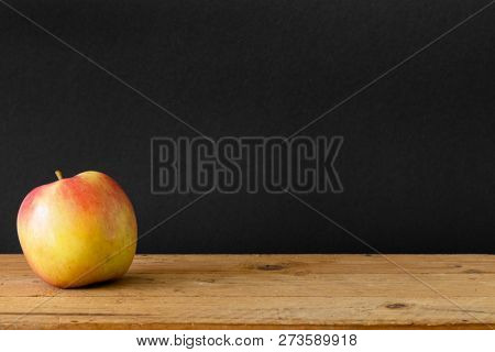 An image of a black background apple wooden table