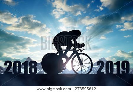 Cyclist ride a road bicycle at sunset. Forward to the New Year 2019.
