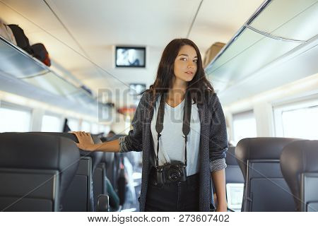 Attractive Woman Photographer With Dslr Camera Standing In Train And Looking At Camera While Traveli