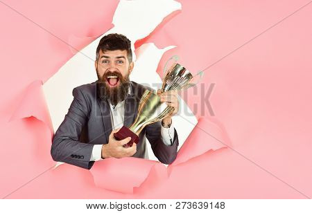 Businessman Celebrating With Trophy Looking Through Hole In Paper. Happy Bearded Man Holds Champion