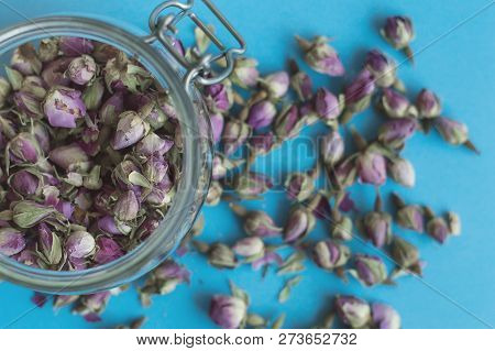 Jar With Dried Rose Flowers On Blue Background. Herbal Tea