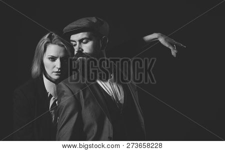 Man And Woman In Retro Suit And Hat On Black Background. Couple In Love With Suspicious Face Working