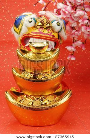 A traditional lion bites a stack of gold ingots,the lion is believed to be able to dispel evil and bring good luck and prosperity in China.