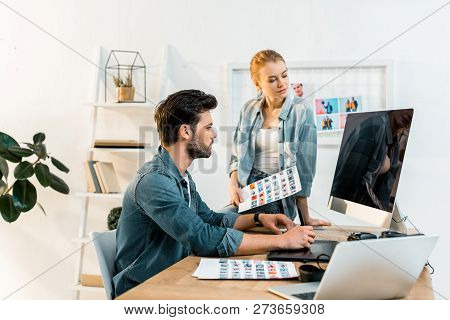 professional young photographers discussing and retouching photos in office poster