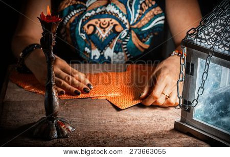 A Woman Lays Out The Tarot Cards By The Light Of A Lantern And A Candle. Selective Focus.