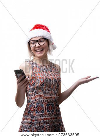 Image of blonde in glasses and Santa's cap with phone in hand on empty space