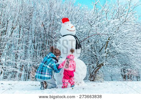 Mother With Daughter Playing Outside In Winter Time. Making Snowman Concept