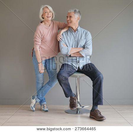 Full length of happy senior couple on grey background