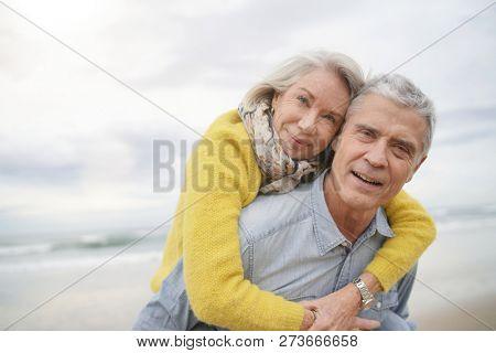 Loving portrait of attractive senior couple on beach in fall