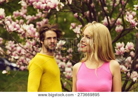 Happy Loving Couple. Portrait Of Beautiful Young Couple Kissing Outdoor In Magnolia Flowers Blossom.