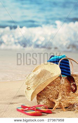 Closeup of summer beach bag with items on sandy beach
