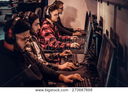Team Of Teenage Gamers Plays In A Multiplayer Video Game On Pc In A Gaming Club.