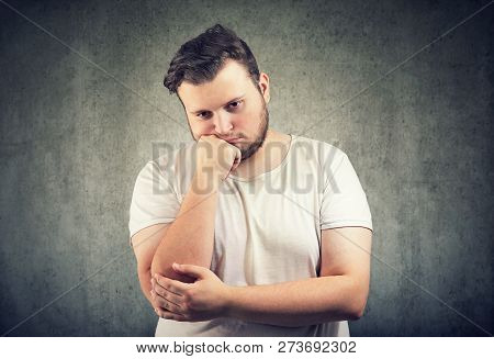 Casual Adult Obese Man Leaning On Hand Having Problem And Looking Unhappy On Gray Background