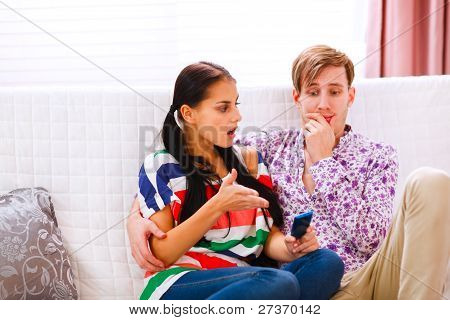 Angry Girl Pointing On Mobile And Looking On Confused Boyfriend