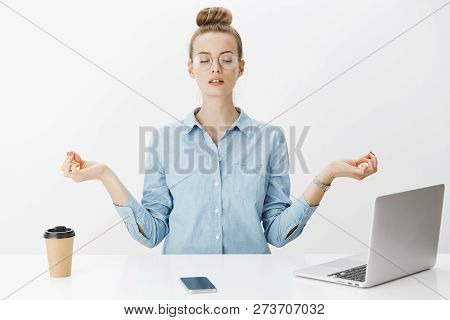 Girl Meditating At Work Sitting In Lotus Pose With Nirvana Orbs Near Laptop And Smartphone Trying Re
