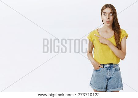 Wow Looks Cool. Amused And Excited Attractive Caucasian Female In Yellow T-shirt Folding Lips From A