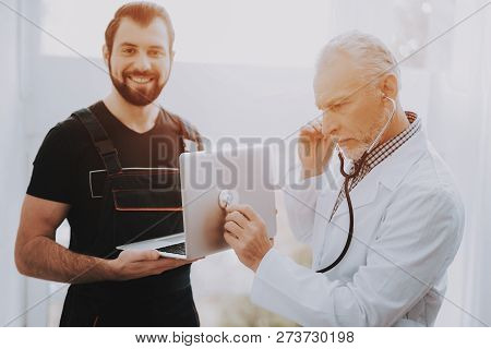 Computer Doctor In White Uniform With Stethoscope. Young Man With Laptop. Examination Of Didital Dev