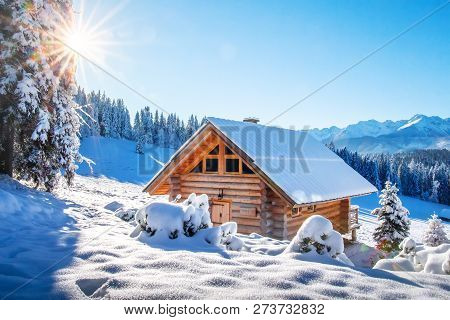 Winter Mountain Landscape With Wooden House On Sunny Clear Day. Alpine Village In Snowy Mountains. A