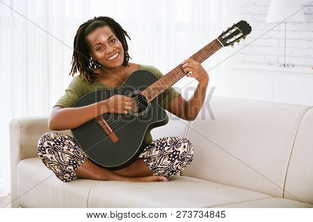 Happy Smilng Young Black Woman Sitting On Sofa And Playing Guitar