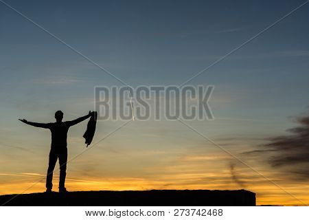 Successful Businessman Celebrating Life Standing On The Edge Of An Old Wall Under Dusk Sky With His