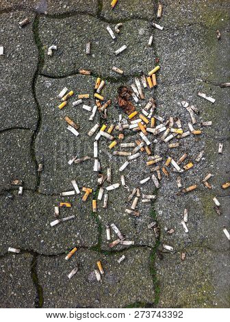 Used Cigarette Butts Spilled On Ground Outdoors.