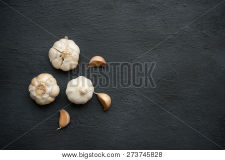 Top view garlic cloves and bulb with copy space on dark background.
