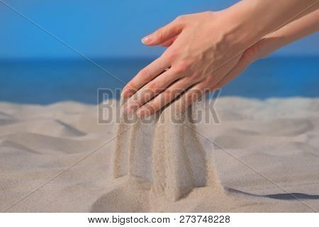 Sand In A Handful Of Hands. Close Up Against Seascape Background. Sand Pours Through Fingers