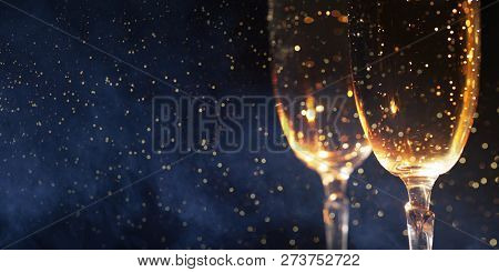Christmas Decoration With Two Glasses Of Champagne And Lights On A Wooden Background, Happy New Year