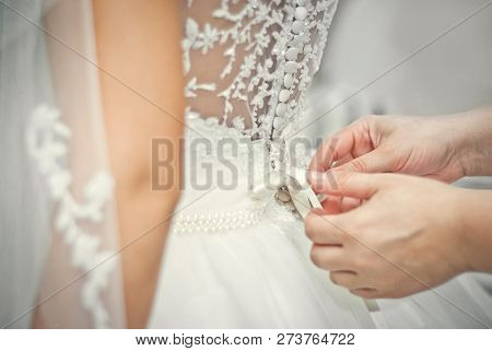Wedding. Mother Preparing Bride For The Wedding Day. Bridesmaid Helps Fasten A Wedding Dress The Bri